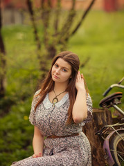 Beautiful young woman in dress sitting on grass near old vintage