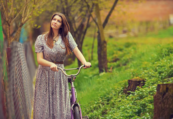 Beautiful young woman in dress walk with old vintage bicycle