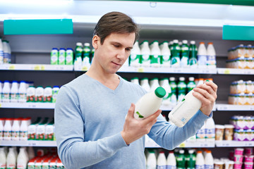 Man chooses dairy products in store
