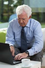 Senior businessman working on a laptop