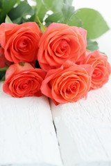 orange roses on a wooden board