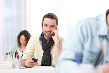 Young attractive student using his mobile during classes