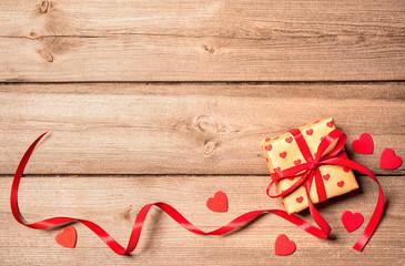 Geschenk mit roter Schleife auf Holzhintergrund