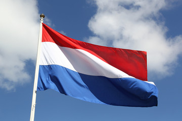 Dutch national flag on liberty day against blue sky with clouds