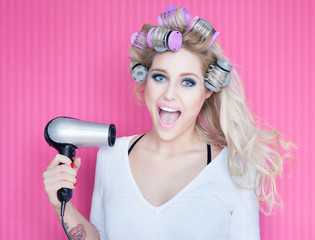 Young attractive woman with hair dryer and curlers