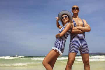 Happy funny couple in retro swimsuit on the beach