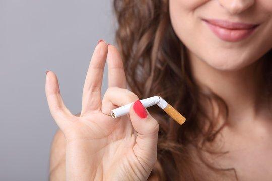 Frau hält durchgebrochene Zigarette