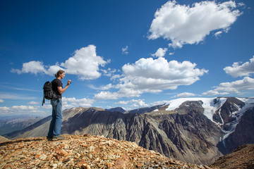 Man with video camera in the mountains