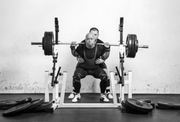 Powerlifter lifting weights helped by his master