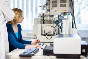 Pretty, female researcher using a microscope in a lab, doing res