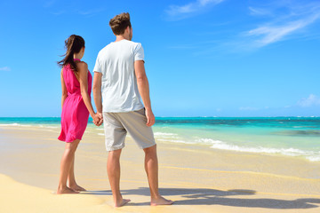 Wall Mural - Beach couple looking at ocean view from behind