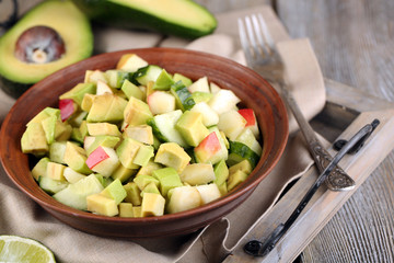 Salad with apple and avocado in bowl on tray on table close up