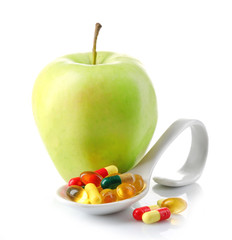 Apple and colorful pills, isolated on white