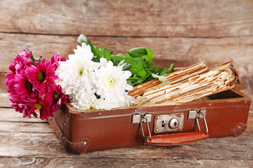 Old wooden suitcase with old books and flowers