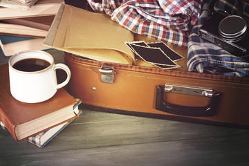 Vintage suitcase open with clothes and books