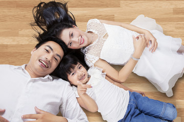 Happy family lying down on the floor