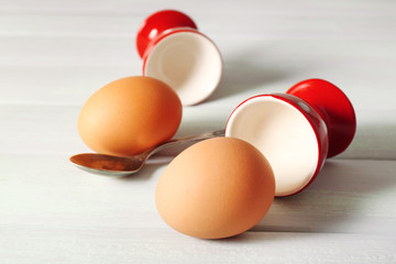 Boiled eggs in holders on light   background