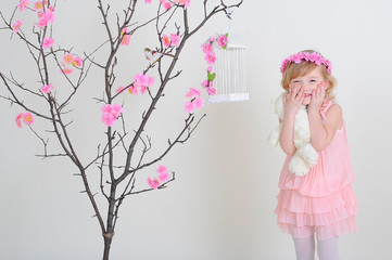 girl in a pink wreath and a pink dress with a bird on a flowerin