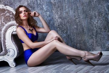 young beautiful woman in blue bikini posing in antique interior