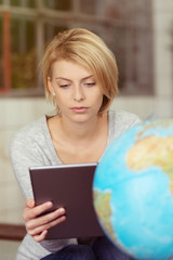junge frau mit globus und tablet-pc