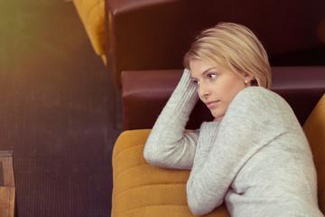 blonde frau entspannt zuhause auf dem sofa