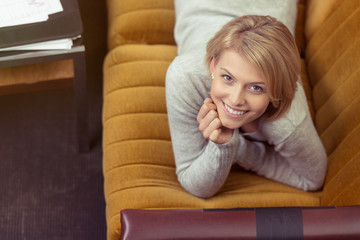 glückliche blonde frau liegt auf einem gelben sofa