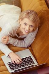 moderne frau liegt mit laptop auf einem gelben sofa