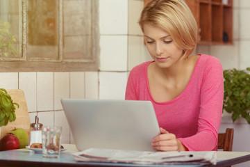 frau sitzt am küchentisch und schaut auf laptop