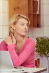 blonde junge frau sitzt mit laptop in der küche