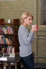 frau lehnt zuhause am schreibtisch mit einer tasse kaffee