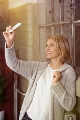 blonde frau fotografiert sich mit ihrem handy