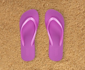 pink beach shoes over yellow sand