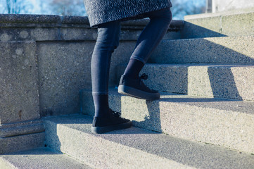 Woman walking up stairs outside