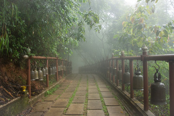 Buddhism bells on hanging from a foggy bridge in a misty forest