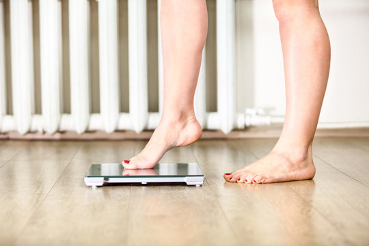 Caucasian female legs gently tread on the floor scales