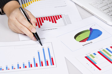 a hand pointing to business chart on the desk