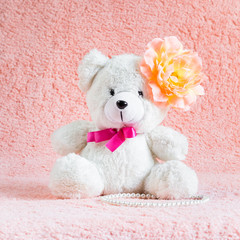 White teddy bear toy with orange flower barrette on head
