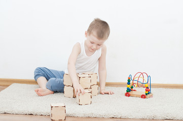 Little kid is playing with blocks