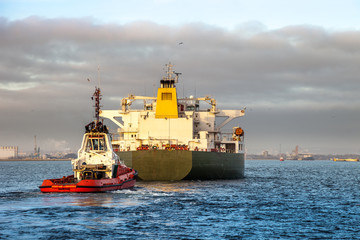 Tanker ship with escorting tug in port.