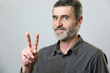 Senior man showing victory sign