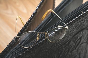 Old vintage round glasses and photo album