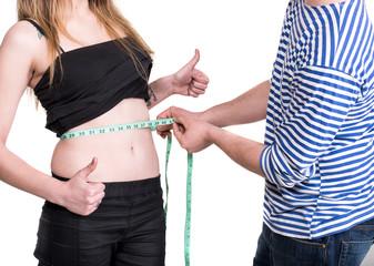 Young man measuring woman's waist