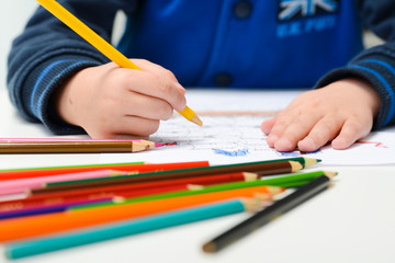 hands of young children drawing with multicolored pencils