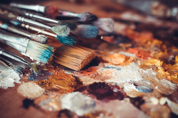 Paintbrushes closeup, artist palette and multicolor paint stains Wall mural