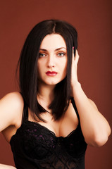 Brunette woman in black dress on the brown background