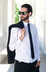 Cool businessman posing with sunglasses outside