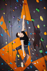 Young man practicing rock-climbing in climbing gym indoors