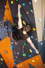 Young man practicing top rope climbing in indoor climbing gym