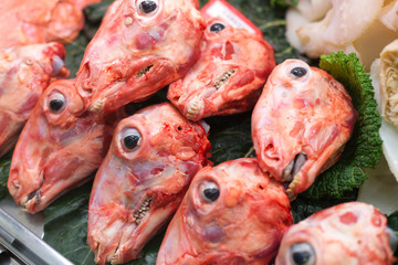 Skinned sheep's heads are lined up for sale at market stall, La