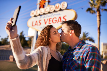 couple kissing and taking selfie by welcome to las vegas sign